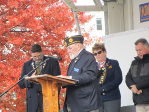 Chaplain Morin officiates with the invocation during the Veterans Day Parade ceremony. Parade Chairman Coldwell, Alderman Barry, State CDR VFW on stage as well.